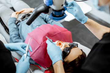 Dentists making dental examination to a young woman with professional microscope © rh2010