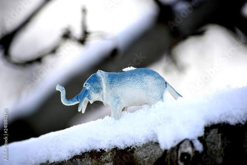 elephant toy figurine on snow, climate change concept