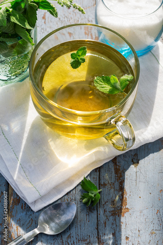 Fresh mint leaf tea in a glass cup on a wooden table, healthcare and healthy eating concept