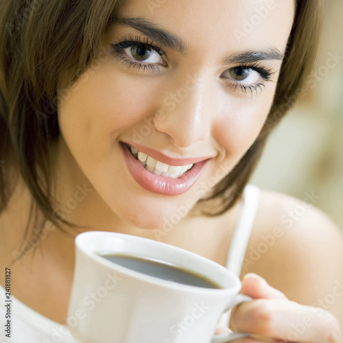 Young happy smiling woman drinking coffee, at home - 241881827