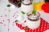 Traditional Italian dessert panna cotta with chocolate sauce and crispy meringue, dessert for Valentine's Day served in glass jars. - 241899028