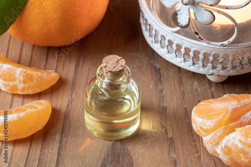 Leinwanddruck Bild A bottle of tangerine essential oil with fresh tangerines
