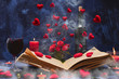 Leinwanddruck Bild - Valentine day. Book in the smoke with flying hearts. Book, hearts, candles, fog, smoke, flowers, wine on a blue background. Magic for lovers. Splash of red wine. A wonderful romantic evening . Love.