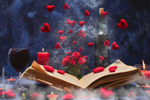Leinwanddruck Bild Valentine day. Book in the smoke with flying hearts. Book, hearts, candles, fog, smoke, flowers, wine on a blue background. Magic for lovers. Splash of red wine. A wonderful romantic evening . Love.