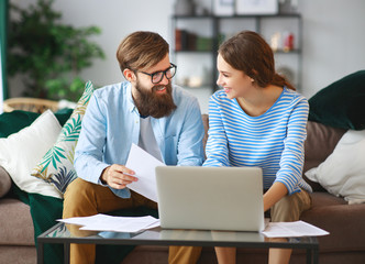married couple with bills receipts documents and laptop at home