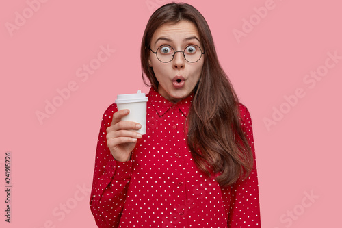 Shocked beautiful woman holds takeaway coffee, opens mouth, surprised to hear rumors, dressed in fashionable clothes, isolated over pink background. Concerned teenager in stupor sees terrible view