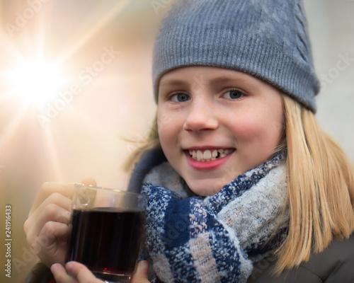 Leinwanddruck Bild Mädchen hält glücklich einen Kinderpunsch als warmes Getränk auf einem Weihnachtsmarkt