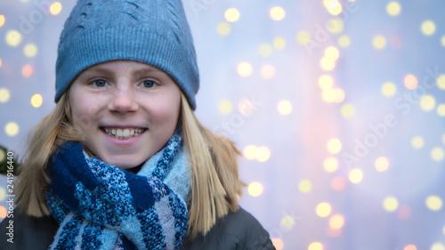 Leinwanddruck Bild Lachendes Mädchen in Winterkleidung vor leuchtendem Bokeh bei einem Fest im Winter
