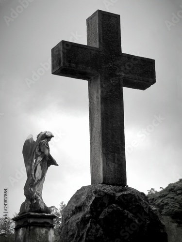 Scene in a graveyard: a large stone religious cross next to a stone statue of an angel. Black and white photo taken on a cloudy day. - 241917864
