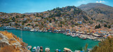 View of beautiful bay with colorful houses on the hillside of the island of Symi. - 241919281