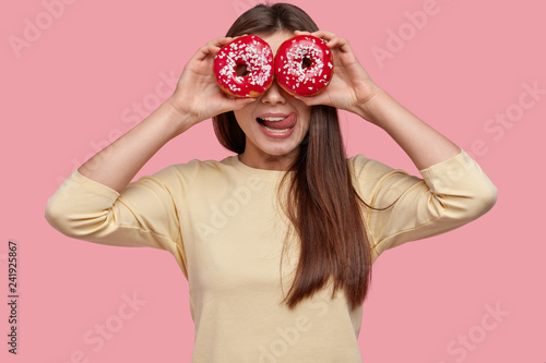 Waist up shot of beautiful young woman shows tongue from pleasant taste, covers eyes with doughnuts, has fun indoor, dressed in yellow clothes, stands over pink background, looks through dessert