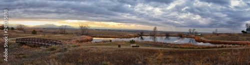 Views of Josh's Pond walking path, Reflecting Sunset in Broomfield Colorado surrounded by Cattails, plains and Rocky mountain landscape during sunset. United States.