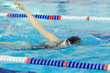 Young girl in goggles and cap swimming front crawl stroke style in the blue water pool.
