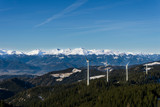Distant view of snowy mountain peaks and windmills - 241949235