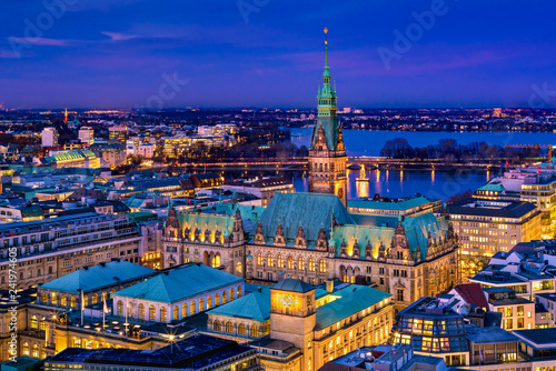 The Hamburg City Hall (German: Rathaus) with downtown and the lake Alster at night. Aerial view.