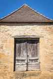 Old brown antique doors in the façade of an authentic French farmhouse silhouetted against a clear blue sky. - 241980601