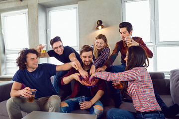 A group of friends with mugs and popcorn at a party indoors © Studio Romantic
