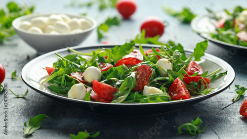 Leinwandbild Motiv Chorizo salad with cherry tomatoes, mozzarella and wild rucola