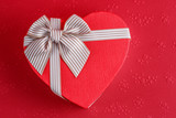 Gift box in the shape of a heart with a ribbon on a red background. The concept is suitable for love stories, birthdays and Valentine's Day - 241985291