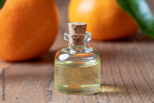 Leinwanddruck Bild A bottle of tangerine essential oil with tangerines