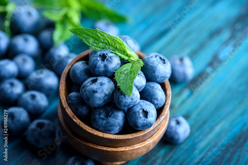 Leinwanddruck Bild Bowl of fresh blueberries on blue rustic wooden table closeup.