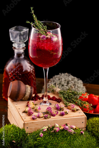 Vertical image of glass with wine alcohol cocktail decorated with cranberry, rosemary and rose flowers at wooden table background.