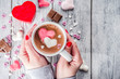 Leinwandbild Motiv Girl hands hold little heart shaped gift box, old wooden table with hot chocolate with marshmallow hearts and tulip flowers, Valentine day background copy space top view, hands in picture flatlay