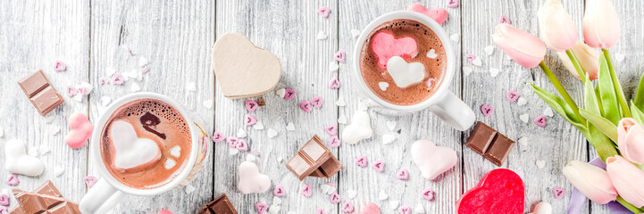 Valentines day treat ideas, two cups hot chocolate drink with marshmallow hearts red pink white color with chocolate pieces, sugar sprinkles, old wooden background copy space top view banner
