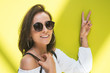 Quadro Young woman with peace sign in front of yellow wall. Trendy girl with sunglasses
