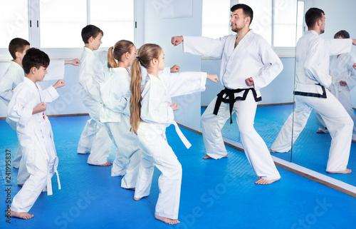 Leinwanddruck Bild Children trying martial moves in karate class