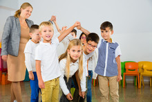 "Постер, картина, фотообои ""Positive female teacher playing circle game with children in classrom"""