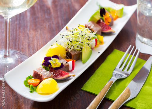 Tasty  fried tuna with mango and avocado, served with fig and flower