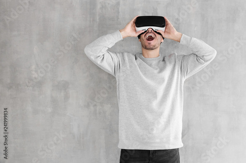 d331a75b2e1 Astonished young man using VR headset