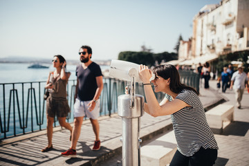 Female tourist visiting Italy.Woman in Syracuse,Sicily.Old town of Syracuse, Ortigia island visitor.Travel destination sightseeing with tourist binoculars.