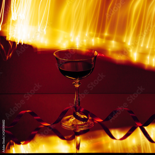 Wine glass, with lines of lights in the background.
