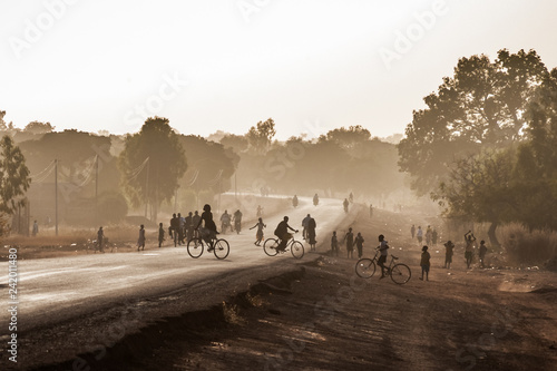 Highway at the exit of Ouagadougou, Burkina Faso, at dusk with silhouetted people. African scenery.