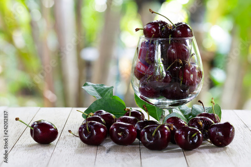 Fresh Cherries in glass and pile of cherries put on old wooden table in green garden