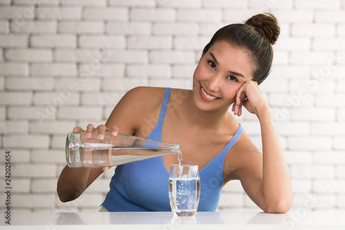 Asian woman pouring water from bottle into glass in the room