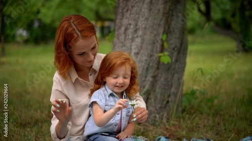 mother and little daughter tell fortune on daisy