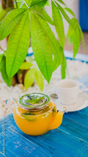 Mango and mint fruit herbal hot tea in transparent glass teapot on a blue wooden table.
