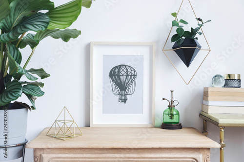 The room interior with mock up photo frame on the retro wooden shelf. Hanging plant in design pot, tropical plant, gold pyramid, design coffe table with books. Concept of minimalistic retro shelf.