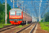 Red passenger electric train moves on a background of green trees and blue sky