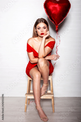 Adorable woman in red dress sitting with red balloon in heart shape