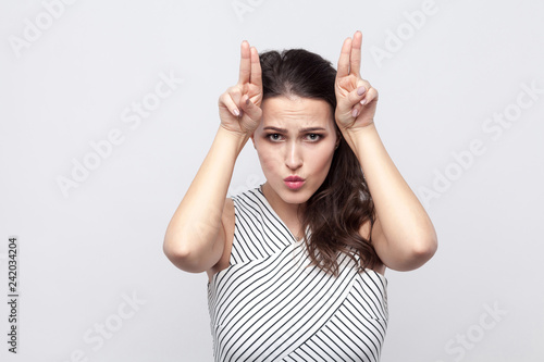 Leinwandbild Motiv Portrait of funny beautiful young brunette woman with makeup and striped dress standing with cow gesture and looking at camera. indoor studio shot, isolated on grey background.