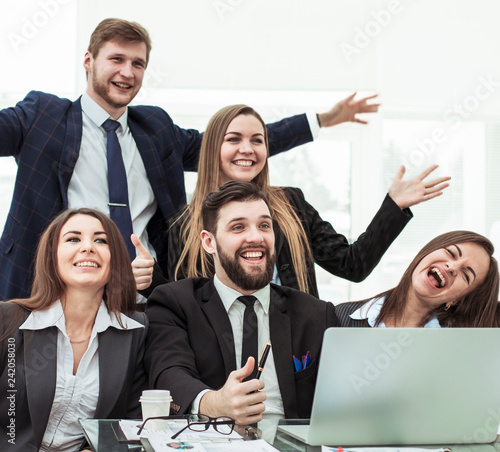 concept of business success - cheering business team in the workplace in the office