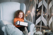 little girl with a Christmas gift sitting in a comfortable chair