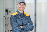 Portrait of a smiling electrician in front of an industrial electric panel in a factory - 242064203