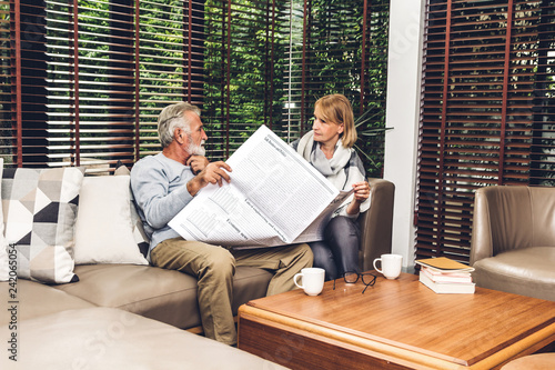 Leinwanddruck Bild Senior couple relax talking and reading newspaper together on sofa in living room at home.Retirement couple concept