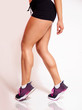 Vertical studio shot, of fit young woman in running shoes with muscular calf /calves