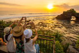 Happiness tourist enjoy their holiday with the beautiful sunset over Pura Batu Bolong an iconic Hinduism sea temple in Bali, Indonesia.